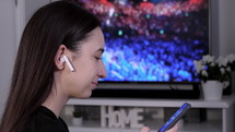 Christian Young woman with wireless earbuds using smartphone while listening worship on smart tv. New technology concept.