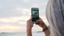 a woman filming the ocean with her cellphone