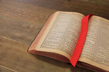 Bookmark between the open pages of a Bible on a wooden desk