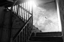 sunlight shining in a stairwell of a basement of an old deserted house