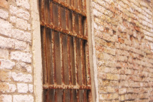 Window with rusting bars and ancient bricks