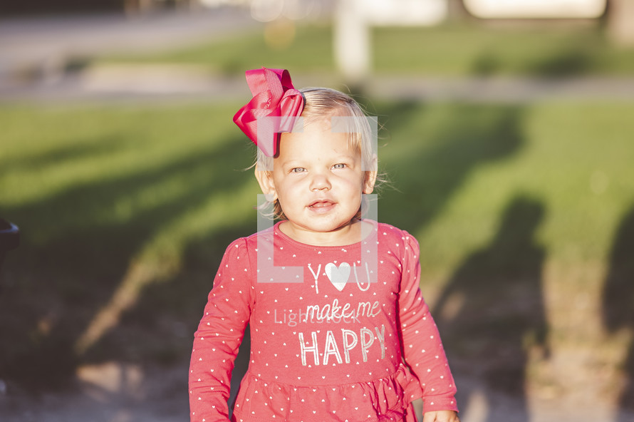 portrait of a toddler girl with a bow