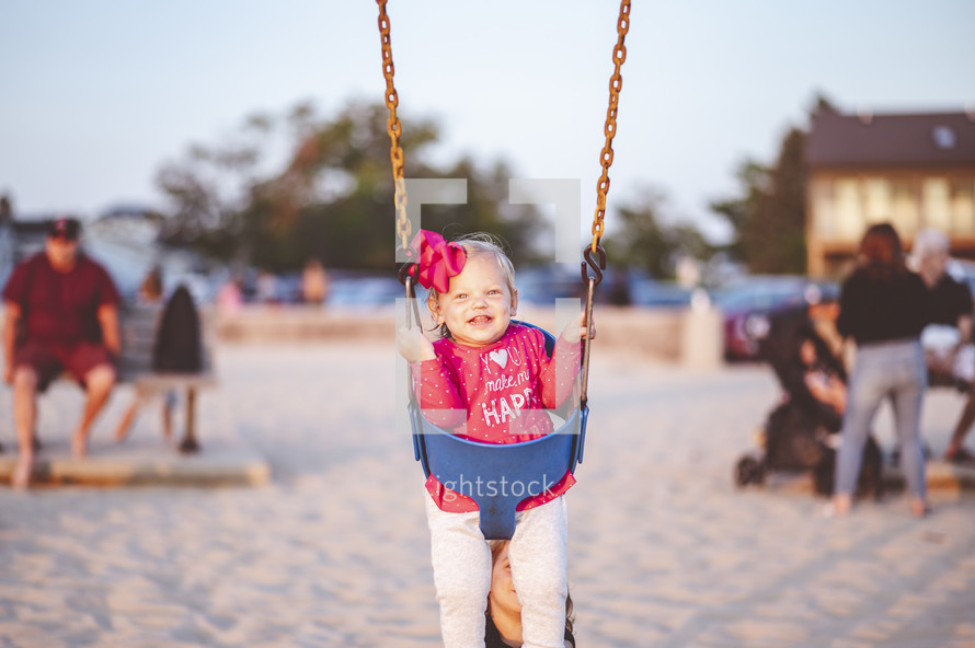little girl on a swing at the beach