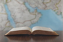 open Bible and map of the Middle East