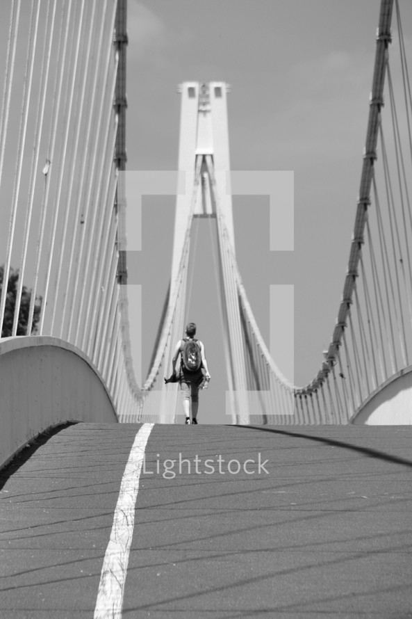 a man walking across a bridge