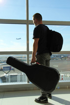 a man holding a guitar case looking out a window at an airport
