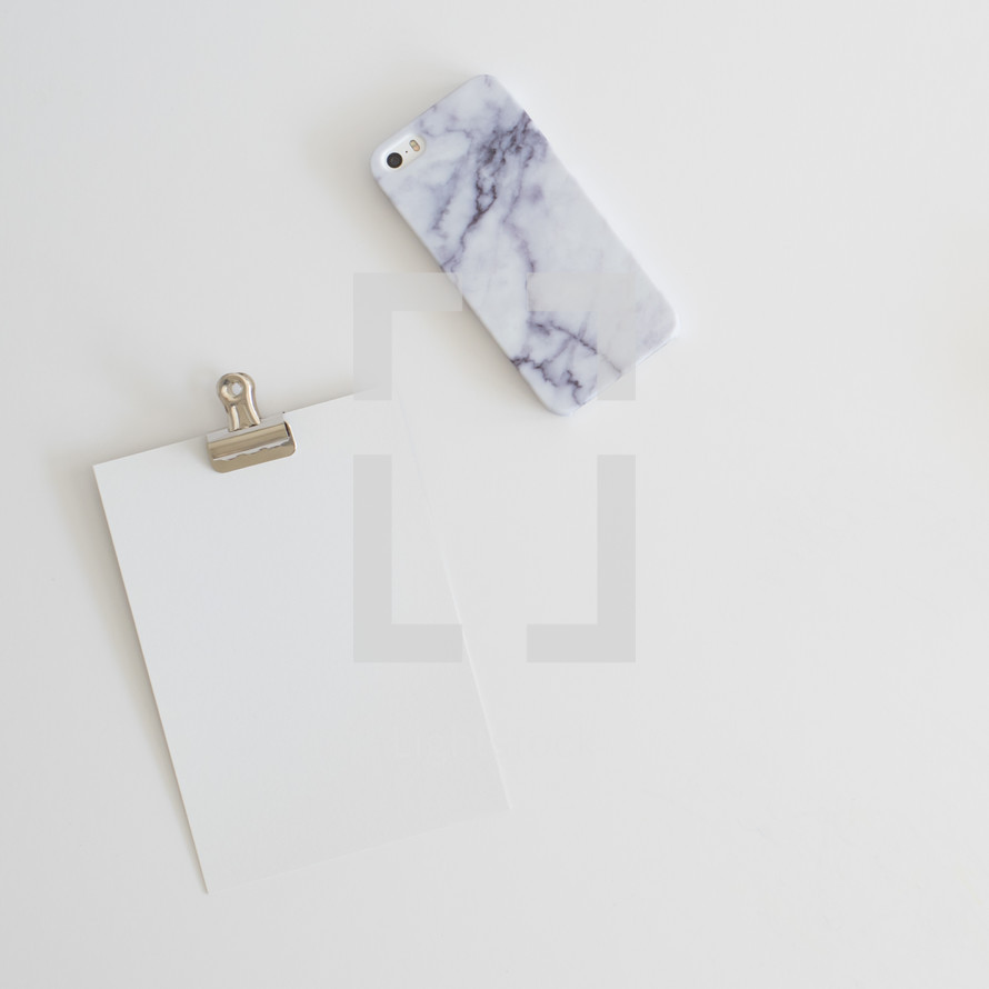 blank paper on a clip and granite patterned cellphone case