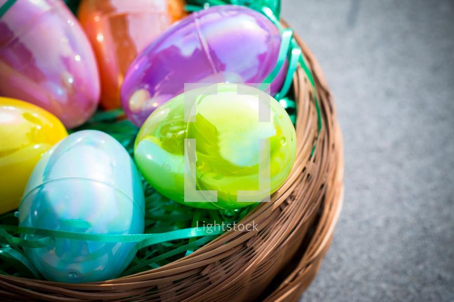 Multi-colored plastic Easter eggs in a circular brown basket