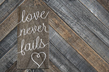 love never fails written on wooden background