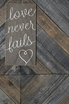 love never fails on wooden background