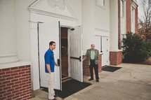 greeters holding church doors open