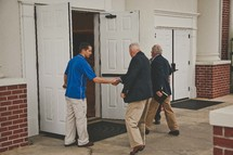 greeters welcoming parishioners at the church door