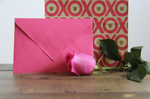 pink rose, envelope, and wrapped gift