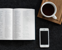 An open Bible next to a cell phone and a cup of coffee.