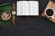 watch, Bible, coffee, tray, and palm fronds on a desk