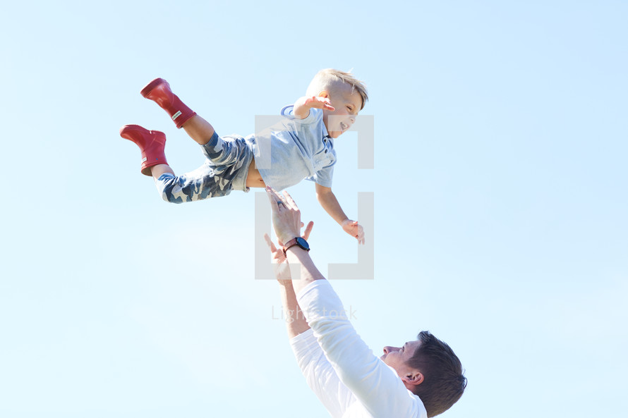 a man tossing her son in the air