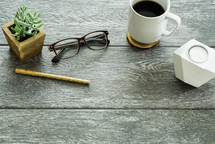 house plant, pen, reading glasses, candle, coffee, and coaster on a table