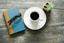 reading glasses, book, coffee cup, saucer, and house plant on a table
