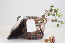 wire basket, linen, fabric, eucalyptus, stamp, twigs, gift tag, ribbon, copper