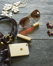contents of a woman's purse, perfume, sunglasses, lipstick, iPhone, necklace, jewelry, earrings