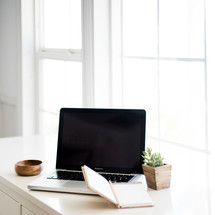 A laptop computer and notebook on a white surface by a windowsill.