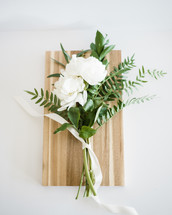 White flowers and greenery tied together and laying on a wooden cutting board.