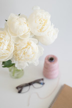 spool of thread, flowers, reading glasses, and notebook