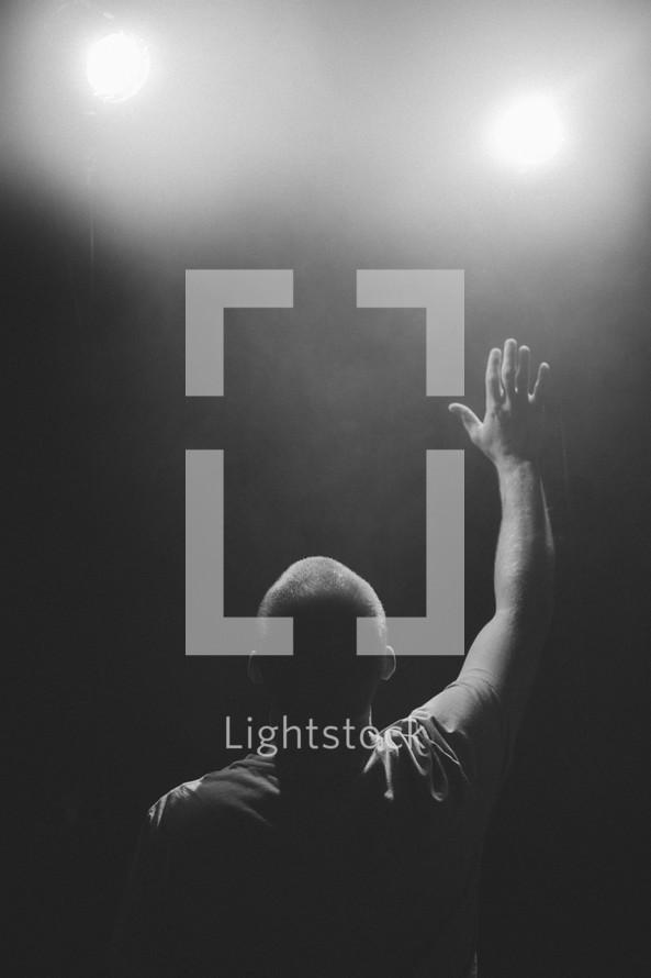 man with raised hand, worship on black