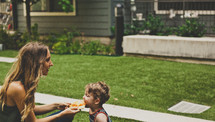 mother and toddler son eating pizza, having a picnic in the grass