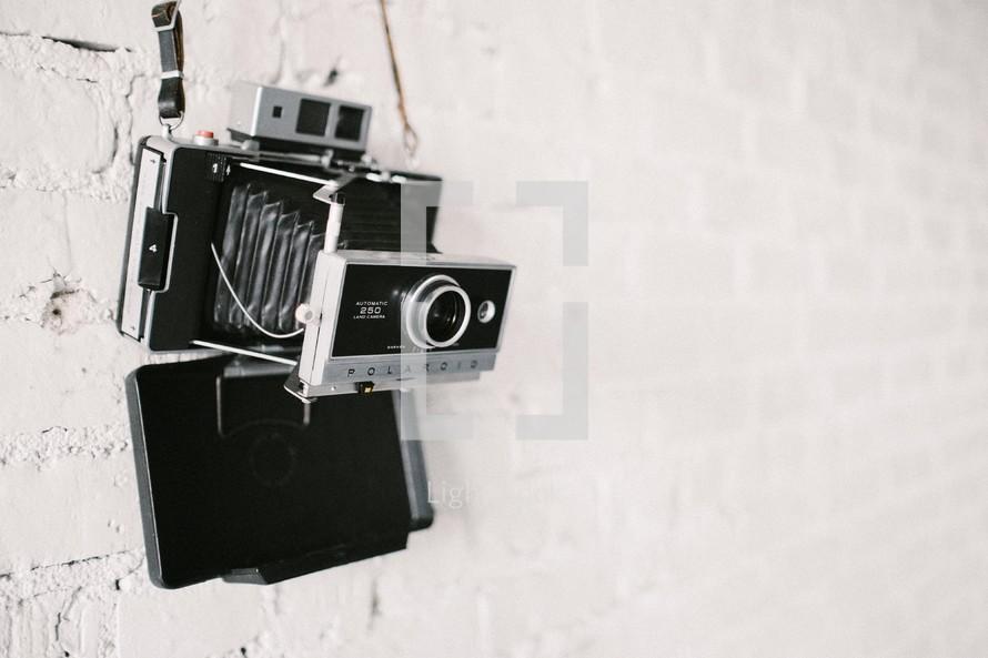 Camera handing on a brick wall.