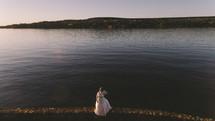 a bride standing at a lake shore at sunset