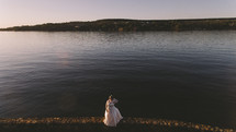 a bride standing at a lake shore at sunset
