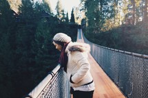 a woman walking across a swinging bridge and looking down