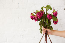 a woman holding a bouquet of dying roses