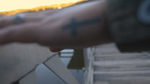a woman with a cross tattoo on her hand touching a railing