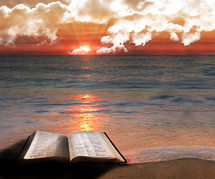 Open Bible on a beach at sunrise as the tide washes over it