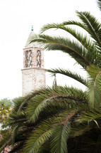 brick tower and palm fronds