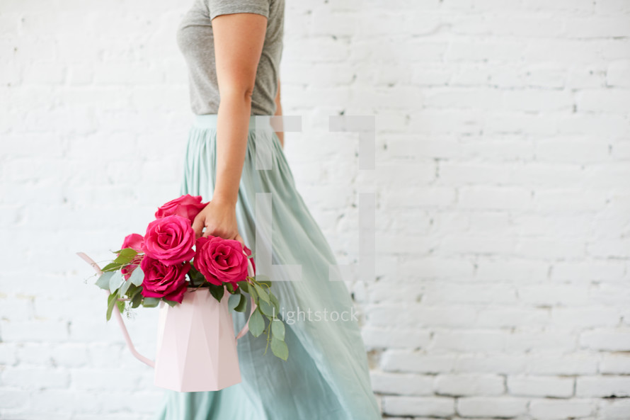 a woman holding a bouquet of flowers in a watering can