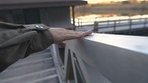 a woman rubbing her hand across a railing on a dock