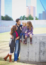 family portrait with daughters sitting on a concrete wall