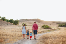 family walking on a dirt road holding hands