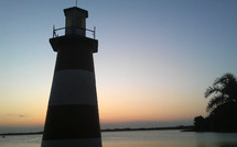 A lighthouse at dusk surrounded by calm water as the sun sets an orange glow along the horizon at dusk.