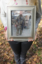 A woman holding a framed photo of a soldier.