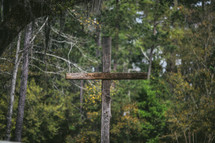 A wooden cross among trees.