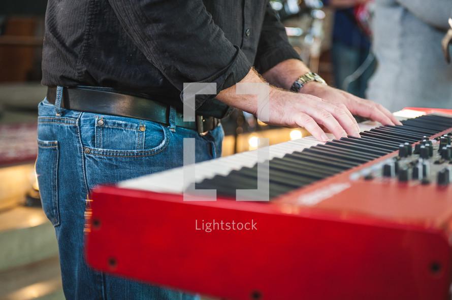 man playing a digital piano