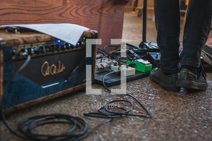 man's feet on guitar foot pedals