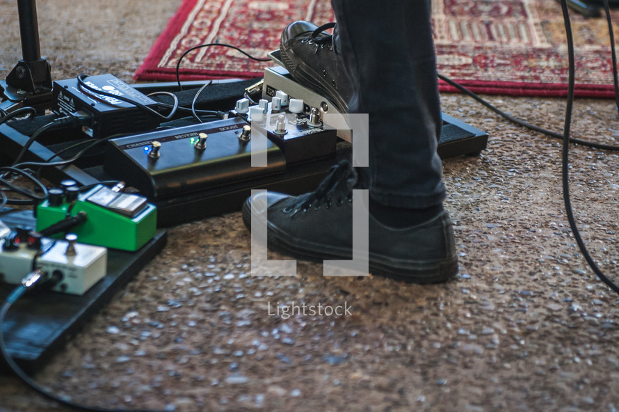 man's foot on a guitar foot pedal