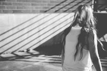 a teen girl walking looking down