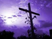 Vines on a cross in front of a purple sky showing that Jesus is the vine and we are the branches. It is the cross of Christ that symbolizes the hope and victory that there is salvation against sin and eternal life in Heaven through Jesus.
