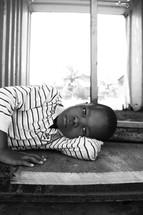 stoic boy child lying down